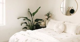 minimalistisches Schlafzimmer; alles weiß mit Pflanzen und Goldakzenten