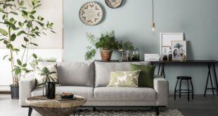 Grünes Haus Wohnzimmer, Rattantisch, graublaue Wand, botanische Kissen Rot